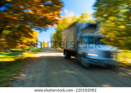 Truck moving down a rural road during fall foliage, Stowe, Vermont, USA - stock photo