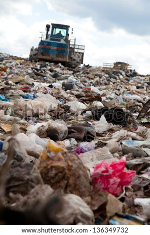 Truck moving garbage in a landfill site - stock photo