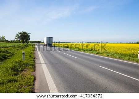 Truck moving the beautiful yellow field countryside road - stock photo