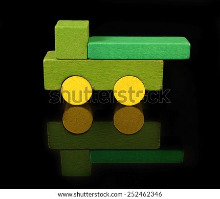 Truck of wooden blocks, traditional toy on black background - stock photo