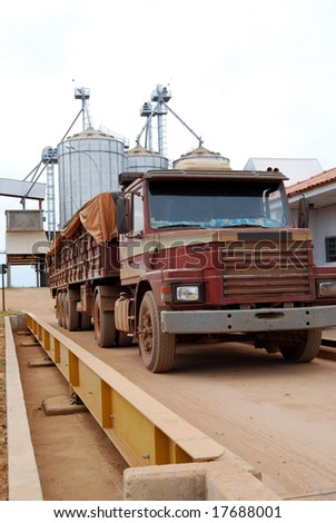 Truck on a scale with a load of soybeans in Brazil, soy storage warehouse and silos in the background - stock photo