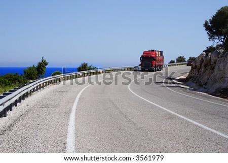 truck on a sunny road at sea coastline - stock photo