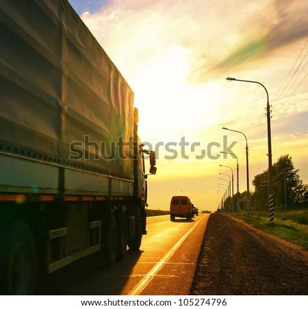 truck on highway, summer sunset - stock photo