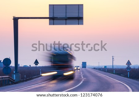 truck on road at sunrise - stock photo