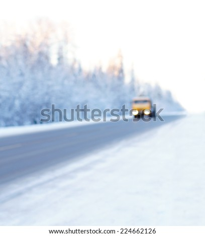 Truck on winter road. Semi truck driving on winter roads by forest. De focused background.  - stock photo