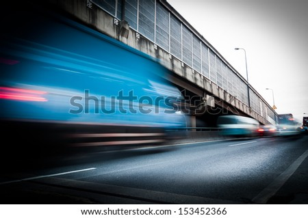 truck speeding through a bridge at sunset,motion blur. - stock photo