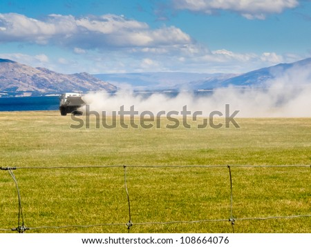 Truck spreading fertilizer on pasture meadow creating an enormous white dust cloud of rock phosphate and potash - stock photo