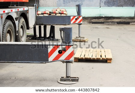 Truck strong outrigger stabilizing legs extended. Boom lifts building material machines on the roof of the house. - stock photo