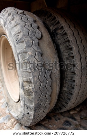 truck tires worn to the extreme with missing treads - stock photo