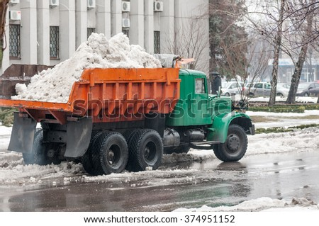 truck transports the snow in the back in the city - stock photo