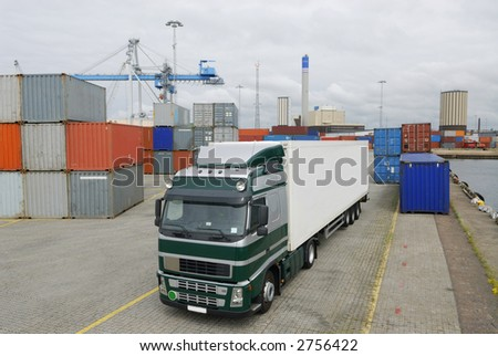 truck waiting in port for cargo, with cranes and containers - stock photo