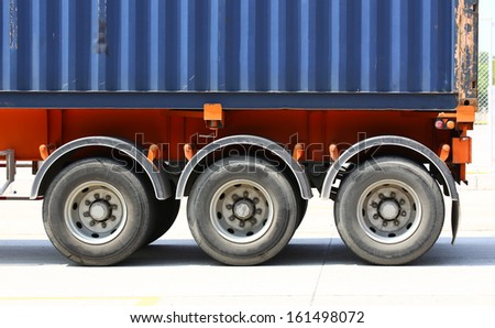 Truck with blue container in shipping  location - stock photo