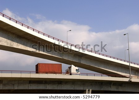 Truck  with container rolling in highway viaduct - stock photo