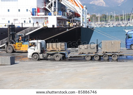 truck with marble in harbor ready to laod ship - stock photo