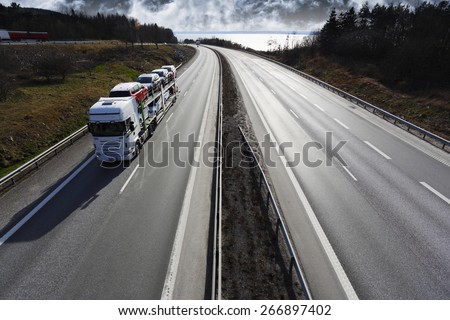 trucking on scenic highway, delivering new cars - stock photo
