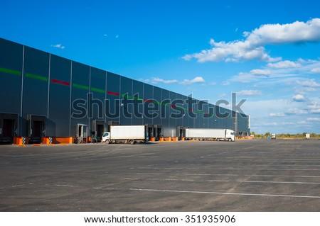 Trucks at big industrial warehouse building - stock photo