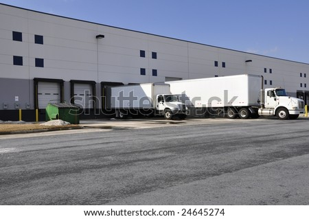 trucks at unloading docks for large warehouse - stock photo