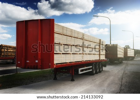 Trucks charged with wood planks waiting for delivery - stock photo