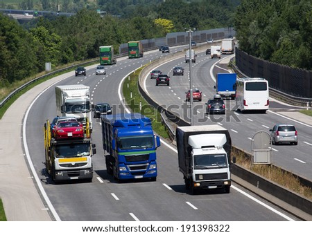 trucks on a three-lane motorway. symbolic photo for transport of goods - stock photo