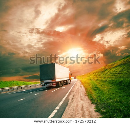 trucks under colorful sky - stock photo