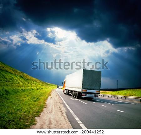 trucks under colorful sky - stock photo