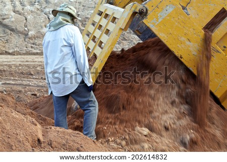 Trucks working on a dam s construction - stock photo