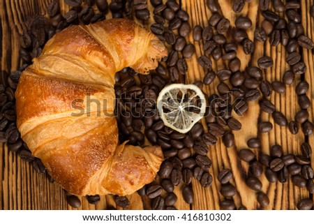 True art. Shot of a croissant and a lemon slice lying on a table full of freshly roasted aromatic coffee beans.  - stock photo
