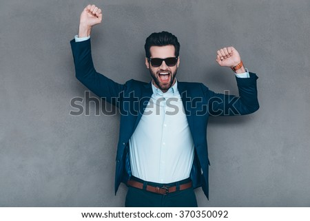 True happiness. Cheerful young handsome man in sunglasses keeping hand on his jacket and looking at camera with smile while standing against grey background - stock photo