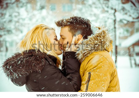 true love. Man and woman happily kissing on the street in the snow. Horizontal color photo - stock photo
