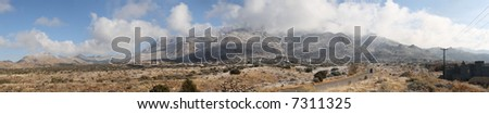 True wide panorama of the Sandia Mountains, next to Albuquerque, New Mexico, covered in snow and the mountaintops obscured by heavy clouds just after the first snow of the winter. - stock photo