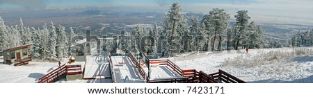 True wide panorama of the top of the ski run on the Sandia Mountains of New Mexico just after the first storm of winter, before any skiers arrive. - stock photo