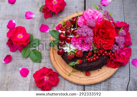 Truffle cake decorated by berries and roses on the rustic wooden table, top view - stock photo