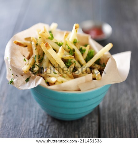 truffle fries standing up in a bowl with wax paper lining - stock photo
