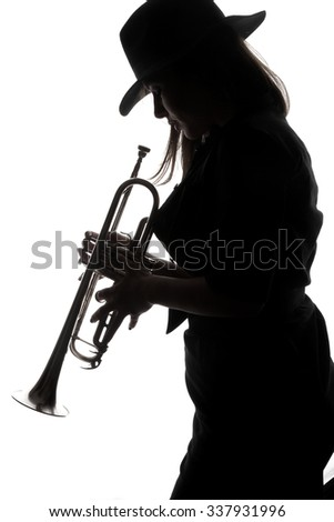 trumpet and a woman - beautiful young woman with a hat playing a trumpet - back light - shadows - musical instruments - trumpet - valves and tubes - mouthpiece for playing