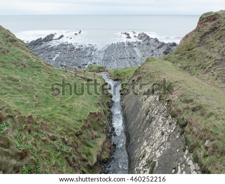 Truncated Waterfall on Blegberry Beach on the Atlantic Coast at Low Tide on the South West Coast Path between Clovelly and Hartland Quay, Devon, England, UK. - stock photo