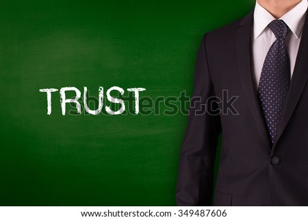 TRUST on Blackboard with businessman - stock photo