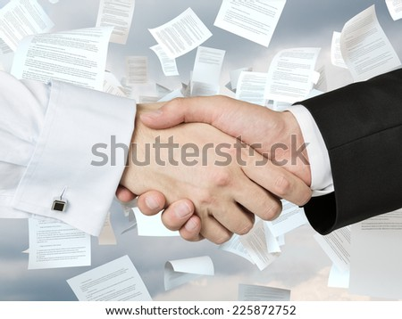Trustful handshake over the flying pages of a contract.
