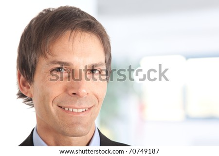 Trustworthy mature businessman portrait in an office environment, smiling. Close-up. - stock photo