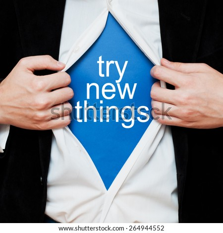 Try new things. Man showing a superhero suit underneath his shirt with a message text written on it. - stock photo