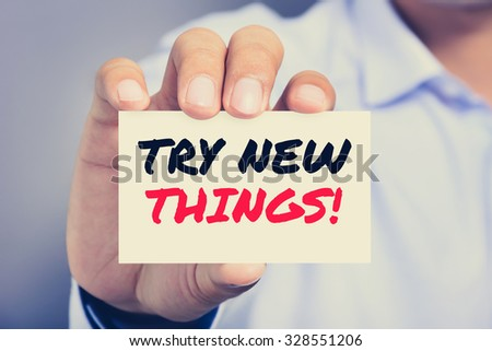 TRY NEW THINGS!, message on the card shown by a man , vintage tone - stock photo