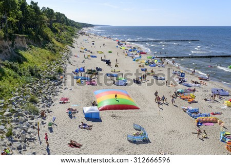 TRZESACZ - AUGUST 13: Tourists enjoy the sunny weather and relaxing on the Baltic sea beach on 13 August 2015 in Trzesacz, Poland.