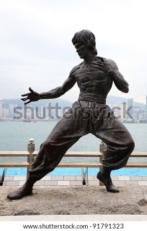 TSIM SHA TSUI, HONG KONG - NOVEMBER 20: Bruce Lee statue on the Avenue of Stars on November 20, 2011 in Tsim Sha Tsui. The statue is one of the main attractions on the famous waterfront promenade. - stock photo
