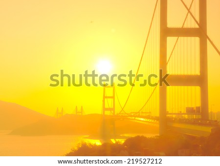 Tsing Ma Bridge in Hong Kong with the sunshine in soft focus - stock photo