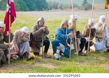 TSIPORI, ISRAEL - JULY 7, 2014: Crusader warriors on their knees at morning prayer before Battle of Hattin reenactment event. This battle marked the fall of Crusaders' Kingdom of Jerusalem in 1187.