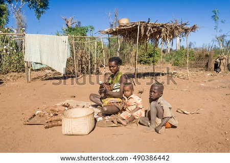 TSIRIBIHINA, MADAGASCAR, JUN 30 2016 : Malagasy family, mom breastfeeding her baby while preparing cassava in a tribal village of Tsiribihina, Madagascar.