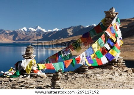 Tso Moriri Lake with prayer flags and himalayas - Rupshu valley, Ladakh, Jammu and Kashmir, India - stock photo