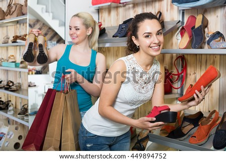 Ttwo glad beautiful young women selecting the shoes and chatting among shelves. Focus on right person  - stock photo