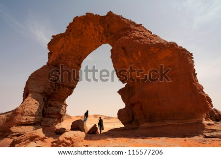 Tuaregs and stone arch in the Sahara Desert - stock photo