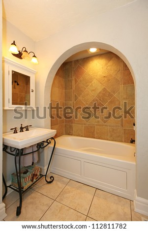 Tub with arch and stone tiles and sink natural bathroom design. - stock photo
