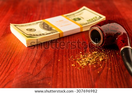 Tube for smoking tobacco and money on a wooden table. Focus on the tube